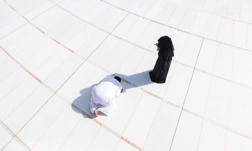 اقتنص صورة بموسم الحج فالهبت مواقع التواصل ،امرأة تظلل زوجها ليصلي